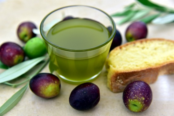 A glass of olive oil, with fresh olives around it, and a piece of bread.